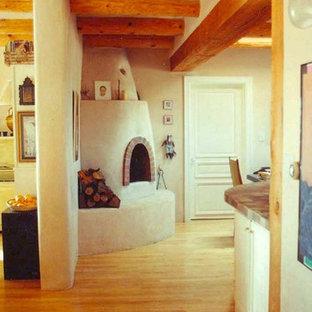 アルバカーキの大きいサンタフェスタイルのおしゃれなキッチン (一体型シンク、フラットパネル扉のキャビネット、白いキャビネット、タイルカウンター、茶色いキッチンパネル、セラミックタイルのキッチンパネル、白い調理設備、淡色無垢フローリング) の写真