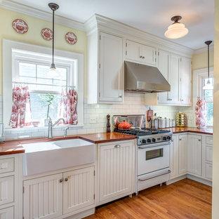Exemple d'une petite cuisine chic en U fermée avec un évier de ferme, un placard à porte affleurante, des portes de placard blanches, une crédence blanche, une crédence en carreau de céramique, un sol en bois brun, un plan de travail en bois, un électroménager blanc et aucun îlot.