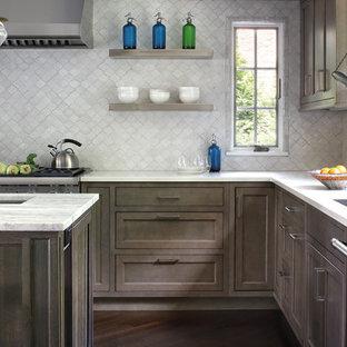 Inspiration för ett vintage l-kök, med en undermonterad diskho, skåp i shakerstil, bruna skåp, grått stänkskydd, rostfria vitvaror, mörkt trägolv, en köksö och brunt golv