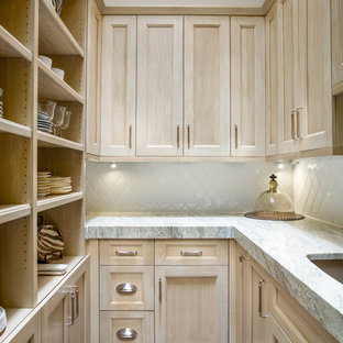 Photo of a mid-sized arts and crafts u-shaped kitchen pantry in Dallas with a farmhouse sink, recessed-panel cabinets, light wood cabinets, quartzite benchtops, white splashback, ceramic splashback, panelled appliances, medium hardwood floors, with island, brown floor and beige benchtop.