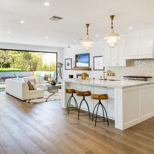 Idéer för ett maritimt vit kök, med skåp i shakerstil, vita skåp, vitt stänkskydd, mellanmörkt trägolv, en köksö och brunt golv