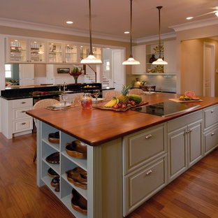 Photo of a tropical open plan kitchen in Hawaii with raised-panel cabinets, wood benchtops and green cabinets.