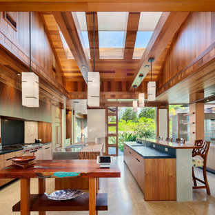 Expansive tropical galley separate kitchen in Hawaii with a double-bowl sink, flat-panel cabinets, medium wood cabinets, wood benchtops, stainless steel appliances and multiple islands.