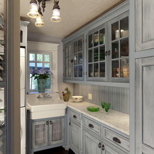 Enclosed kitchen - traditional l-shaped enclosed kitchen idea in Portland with glass-front cabinets, blue cabinets, a farmhouse sink, marble countertops and blue backsplash