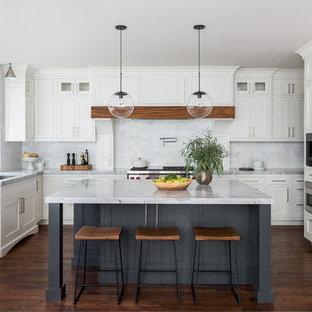 シアトルの広いトランジショナルスタイルのおしゃれなキッチン (アンダーカウンターシンク、シェーカースタイル扉のキャビネット、白いキャビネット、白いキッチンパネル、大理石のキッチンパネル、パネルと同色の調理設備、濃色無垢フローリング、茶色い床、大理石カウンター、グレーのキッチンカウンター) の写真