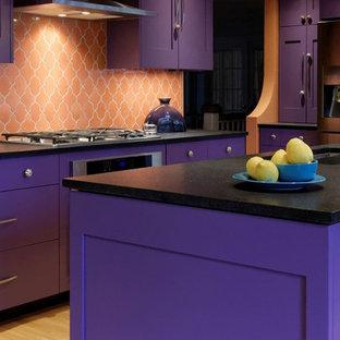 Bild på ett avskilt, stort medelhavsstil svart svart l-kök, med en undermonterad diskho, skåp i shakerstil, lila skåp, bänkskiva i kvarts, orange stänkskydd, stänkskydd i keramik, rostfria vitvaror, ljust trägolv, en köksö och brunt golv