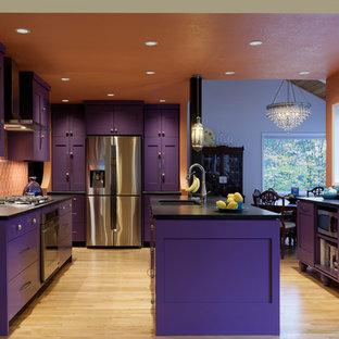 Inspiration för avskilda, stora medelhavsstil svart l-kök, med en undermonterad diskho, skåp i shakerstil, lila skåp, bänkskiva i kvarts, orange stänkskydd, stänkskydd i keramik, rostfria vitvaror, ljust trägolv, en köksö och brunt golv