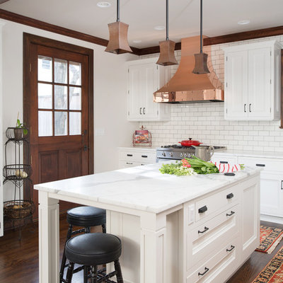 Inspiration for a large transitional l-shaped dark wood floor enclosed kitchen remodel in Kansas City with a farmhouse sink, recessed-panel cabinets, white cabinets, marble countertops, white backsplash, subway tile backsplash, stainless steel appliances and an island