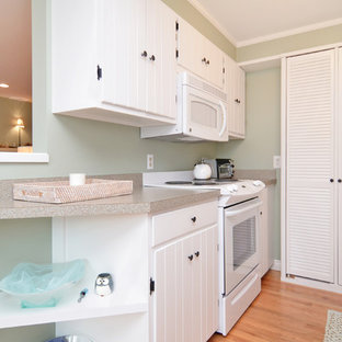 Design ideas for a small beach style galley eat-in kitchen in Seattle with beaded inset cabinets, white cabinets, laminate benchtops, white appliances and light hardwood floors.