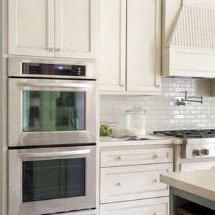 Inspiration for a mid-sized transitional u-shaped eat-in kitchen remodel in Little Rock with a farmhouse sink, recessed-panel cabinets, white cabinets, quartz countertops, white backsplash, subway tile backsplash, stainless steel appliances and an island