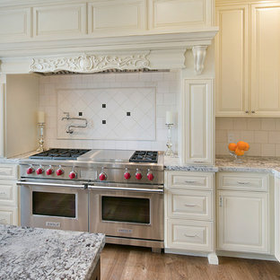 Inspiration for a large victorian l-shaped kitchen/diner in San Francisco with a submerged sink, raised-panel cabinets, white cabinets, granite worktops, white splashback, stone tiled splashback, stainless steel appliances, medium hardwood flooring, an island, brown floors and multicoloured worktops.