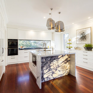 Inspiration for a large contemporary u-shaped eat-in kitchen in Melbourne with an undermount sink, white cabinets, marble benchtops, window splashback, dark hardwood floors, with island, brown floor, white benchtop, recessed-panel cabinets and stainless steel appliances.