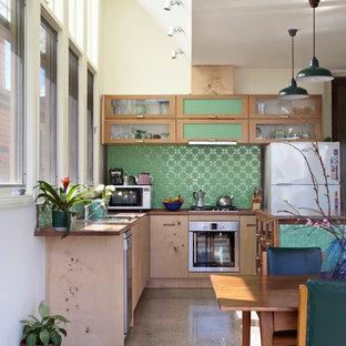 Immagine di una cucina minimal di medie dimensioni con ante di vetro, ante in legno scuro, top in legno, paraspruzzi verde, elettrodomestici bianchi, pavimento in cemento, isola, lavello a vasca singola, paraspruzzi con piastrelle di metallo, pavimento grigio e top marrone
