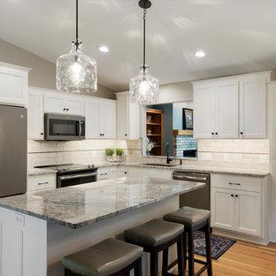 Foto di una cucina con lavello sottopiano, ante in stile shaker, ante turchesi, top in granito, paraspruzzi con piastrelle in ceramica, parquet chiaro e isola