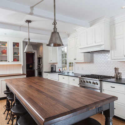 Inspiration for a large transitional l-shaped light wood floor and brown floor eat-in kitchen remodel in Philadelphia with a single-bowl sink, white backsplash, subway tile backsplash, stainless steel appliances, recessed-panel cabinets, white cabinets, an island, soapstone countertops and black countertops