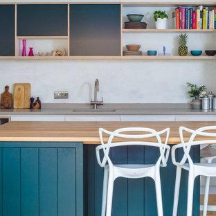 Offene, Mittelgroße Moderne Küche in L-Form mit Einbauwaschbecken, flächenbündigen Schrankfronten, Quarzwerkstein-Arbeitsplatte, Küchengeräten aus Edelstahl, braunem Holzboden, Kücheninsel, braunem Boden und beiger Arbeitsplatte in Oxfordshire