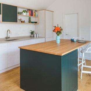 Foto de cocina en L, contemporánea, de tamaño medio, abierta, con fregadero encastrado, armarios con paneles lisos, electrodomésticos de acero inoxidable, una isla, encimeras beige, puertas de armario naranjas, encimera de madera, suelo de madera clara y suelo beige