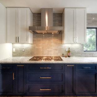 Große Moderne Wohnküche in U-Form mit Landhausspüle, Schrankfronten im Shaker-Stil, weißen Schränken, Küchenrückwand in Beige, Rückwand aus Porzellanfliesen, Küchengeräten aus Edelstahl, hellem Holzboden, Kücheninsel, gelbem Boden und weißer Arbeitsplatte in San Diego