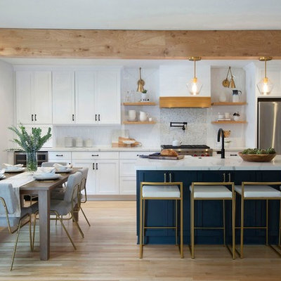 Inspiration for a mid-sized transitional galley light wood floor and beige floor open concept kitchen remodel in Denver with shaker cabinets, white cabinets, quartz countertops, an island, white countertops, a farmhouse sink, white backsplash, ceramic backsplash and stainless steel appliances