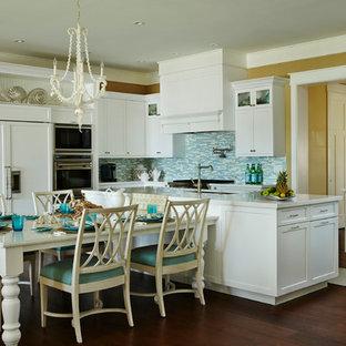 Große Maritime Wohnküche in U-Form mit Unterbauwaschbecken, Schrankfronten im Shaker-Stil, weißen Schränken, Küchenrückwand in Blau, Rückwand aus Glasfliesen, Küchengeräten aus Edelstahl, dunklem Holzboden, Kücheninsel und braunem Boden in Miami