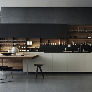 Imagen de cocina en L, actual, con puertas de armario negras, electrodomésticos negros, armarios con paneles lisos, salpicadero negro, suelo de cemento y encimeras negras