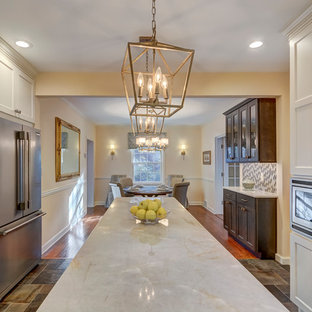 Traditional eat-in kitchen appliance - Example of a classic galley eat-in kitchen design in St Louis with an undermount sink, white cabinets, granite countertops and an island