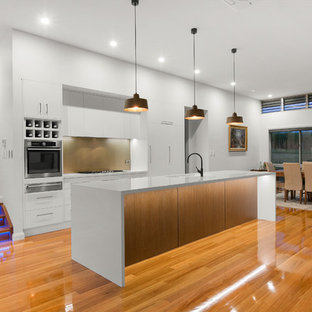 Contemporary eat-in kitchen in Other with a single-bowl sink, flat-panel cabinets, white cabinets, brown splashback, glass sheet splashback, stainless steel appliances, medium hardwood floors, with island and white benchtop.