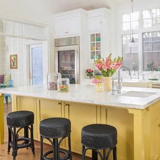 ロサンゼルスの巨大なカントリー風おしゃれなキッチン (エプロンフロントシンク、シェーカースタイル扉のキャビネット、黄色いキャビネット、大理石カウンター、白いキッチンパネル、セラミックタイルのキッチンパネル、シルバーの調理設備、淡色無垢フローリング、ベージュの床) の写真