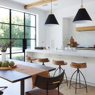 Exempel på ett stort klassiskt gul gult kök, med en undermonterad diskho, skåp i shakerstil, vita skåp, marmorbänkskiva, vitt stänkskydd, stänkskydd i tunnelbanekakel, integrerade vitvaror, ljust trägolv och en köksö