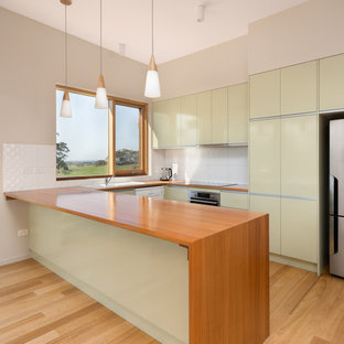 Design ideas for a mid-sized contemporary l-shaped eat-in kitchen in Other with green cabinets, wood benchtops, white splashback, ceramic splashback, light hardwood floors, a drop-in sink, flat-panel cabinets, stainless steel appliances, a peninsula, beige floor and brown benchtop.