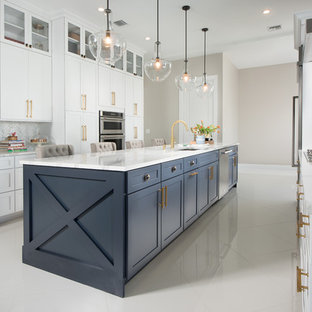 Design ideas for a transitional galley kitchen in Miami with an undermount sink, shaker cabinets, white cabinets, white splashback, marble splashback, stainless steel appliances, with island and white floor.