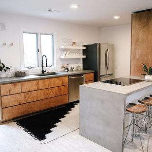Foto di una cucina abitabile minimalista con lavello sottopiano, ante lisce, ante in legno scuro, top in cemento, elettrodomestici in acciaio inossidabile, pavimento in laminato e penisola