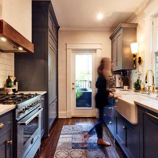 Ejemplo de cocina de galera, tradicional, cerrada, sin isla, con fregadero sobremueble, armarios estilo shaker, puertas de armario azules, salpicadero blanco, salpicadero de azulejos tipo metro, electrodomésticos de acero inoxidable y suelo de madera oscura