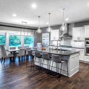 Cette photo montre une cuisine américaine chic en L avec un évier encastré, des portes de placard blanches, un plan de travail en onyx, une crédence en carrelage métro, un électroménager en acier inoxydable, un sol en bois foncé et un îlot central.