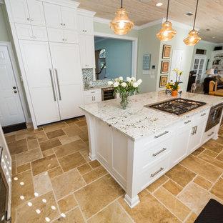 Foto di una cucina stile marino con lavello a vasca singola, ante in stile shaker, ante bianche, top in granito, paraspruzzi verde, paraspruzzi con lastra di vetro, elettrodomestici da incasso e pavimento in travertino