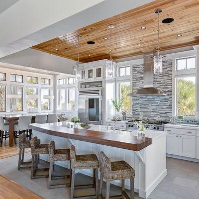 Example of a beach style l-shaped kitchen design in Jacksonville with matchstick tile backsplash, marble countertops, shaker cabinets, white cabinets, stainless steel appliances and multicolored backsplash