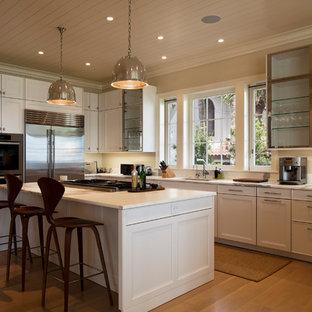 Idéer för maritima kök, med en undermonterad diskho, luckor med lamellpanel, gula skåp, marmorbänkskiva, stänkskydd i sten, rostfria vitvaror, ljust trägolv, en köksö och vitt stänkskydd