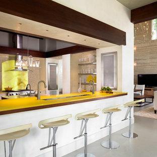 Idéer för funkis gult u-kök, med gult stänkskydd, stänkskydd i sten, rostfria vitvaror, luckor med glaspanel och skåp i rostfritt stål