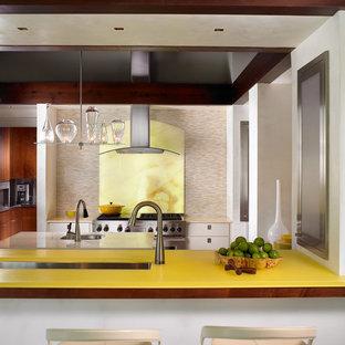 Foto di una cucina contemporanea chiusa con lavello sottopiano, ante lisce, paraspruzzi giallo, paraspruzzi in lastra di pietra, elettrodomestici in acciaio inossidabile e top giallo