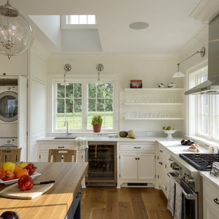 Farmhouse enclosed kitchen photos - Inspiration for a country medium tone wood floor enclosed kitchen remodel in New York with an undermount sink, recessed-panel cabinets, white cabinets, white backsplash, stainless steel appliances and an island