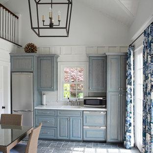 Неиссякаемый источник вдохновения для домашнего уюта: маленькая параллельная кухня-гостиная в классическом стиле с накладной раковиной, фасадами с выступающей филенкой, синими фасадами, столешницей из акрилового камня, техникой из нержавеющей стали и полом из сланца без острова