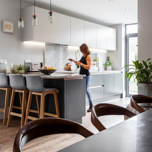 Inspiration for a contemporary l-shaped kitchen in Dorset with flat-panel cabinets, white cabinets, grey splashback, stone slab splashback, light hardwood flooring, a breakfast bar and grey worktops.
