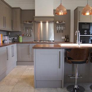 ドーセットの中サイズのインダストリアルスタイルのおしゃれなキッチン (ドロップインシンク、シェーカースタイル扉のキャビネット、グレーのキャビネット、ラミネートカウンター、グレーのキッチンパネル、黒い調理設備、セラミックタイルの床) の写真