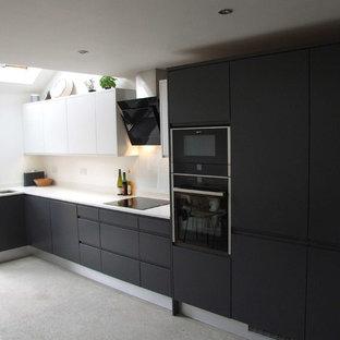ドーセットの中くらいのコンテンポラリースタイルのおしゃれなキッチン (ドロップインシンク、フラットパネル扉のキャビネット、グレーのキャビネット、人工大理石カウンター、白いキッチンパネル、ガラス板のキッチンパネル、黒い調理設備、クッションフロア、アイランドなし) の写真
