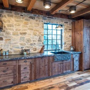 Idée de décoration pour une cuisine ouverte chalet en L de taille moyenne avec un évier de ferme, des portes de placard en bois brun, un plan de travail en granite, un électroménager encastrable, un sol en bois brun, une péninsule, un sol marron et un plan de travail multicolore.