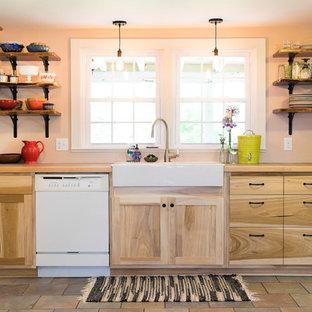 Cette photo montre une cuisine américaine nature en L de taille moyenne avec un évier de ferme, un placard à porte plane, des portes de placard en bois clair, un plan de travail en carrelage, un électroménager blanc, un sol en carrelage de céramique et aucun îlot.