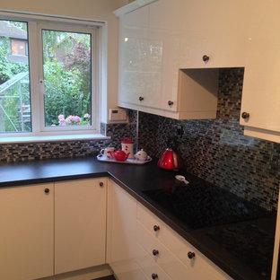 Foto på ett avskilt, litet funkis u-kök, med en rustik diskho, släta luckor, vita skåp, stänkskydd i mosaik och svarta vitvaror