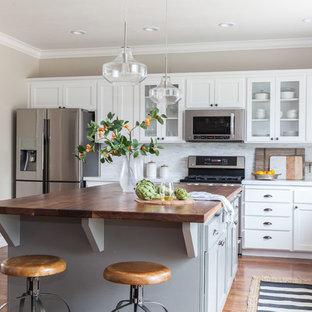 Mittelgroße Country Wohnküche in U-Form mit Unterbauwaschbecken, Schrankfronten im Shaker-Stil, grauen Schränken, Quarzit-Arbeitsplatte, Küchenrückwand in Grau, Rückwand aus Steinfliesen, Küchengeräten aus Edelstahl, braunem Holzboden und Kücheninsel in Sacramento