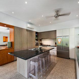 ブリスベンの大きいトロピカルスタイルのおしゃれなキッチン (ドロップインシンク、フラットパネル扉のキャビネット、中間色木目調キャビネット、大理石カウンター、白いキッチンパネル、ガラス板のキッチンパネル、コンクリートの床) の写真