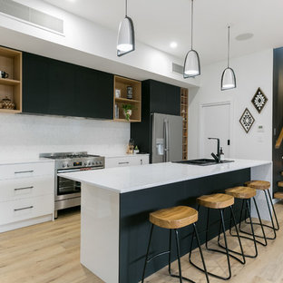 Photo of a contemporary galley kitchen in Adelaide with a drop-in sink, flat-panel cabinets, white cabinets, white splashback, stainless steel appliances, light hardwood floors, with island, beige floor and white benchtop.